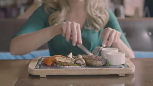 frauenhand ein steak im restaurant slowmo schneiden - steak stock-videos und b-roll-filmmaterial