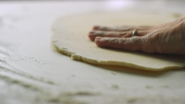 A Woman's Hands Turn Over a Large, Flat Piece of Pastry Dough and Smooth It Out on a Lightly-Floured Surface