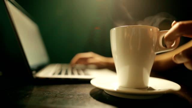 vídeos y material grabado en eventos de stock de manos de mujer escribiendo en un teclado de ordenador portátil - café bebida