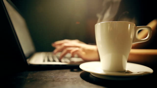 Woman's hands typing on a laptop keyboard, with coffe cup