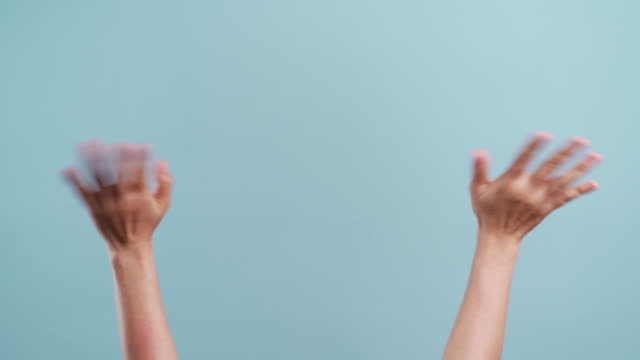 Woman's hands waving hand gesturing on copy space and moving sign language isolated over blue background