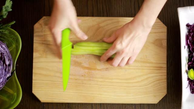 vídeos de stock e filmes b-roll de woman's hands with a knife cut red cabbage salad. cut cucumber - crucíferas