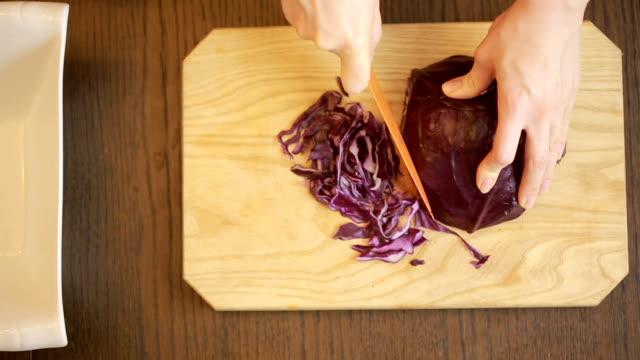 vídeos de stock e filmes b-roll de woman's hands with a knife cut red cabbage salad - crucíferas