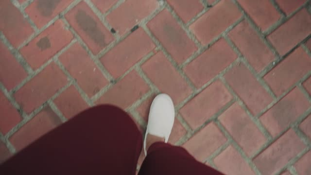 pov of woman's hipster foot while walking with brick abstract floor - prospettiva del fotografo video stock e b–roll