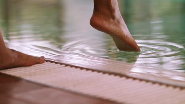 kvinnans ben vid poolen känsla vattentemperaturen - på gränsen bildbanksvideor och videomaterial från bakom kulisserna