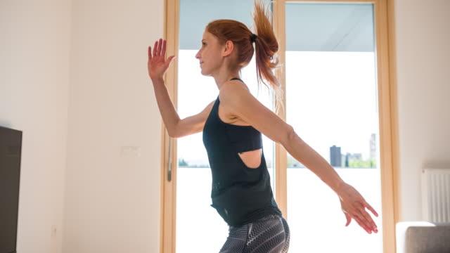 kvinnans ben hoppar omväxlande fram och tillbaka - hemmaträning bildbanksvideor och videomaterial från bakom kulisserna