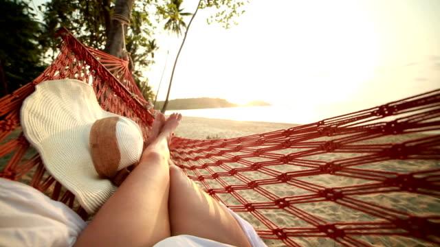 le gambe della donna sull'amaca in isola tropicale. pov - amaca video stock e b–roll