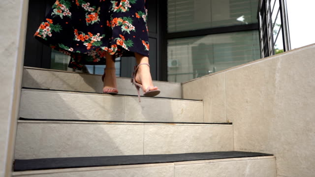 Woman's legs stepping down on stairs