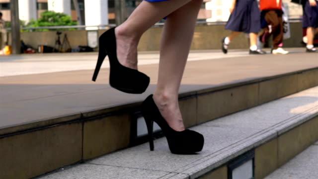 vídeos de stock, filmes e b-roll de pernas da mulher descendo na escada na cidade. - salto alto