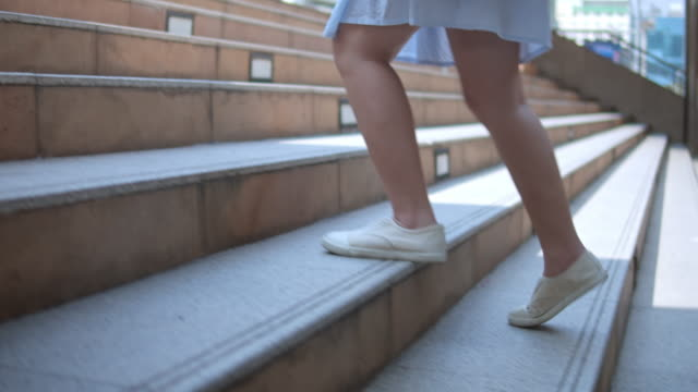 woman's legs stepping up on stairway in the city,slow motion - fare un passo video stock e b–roll