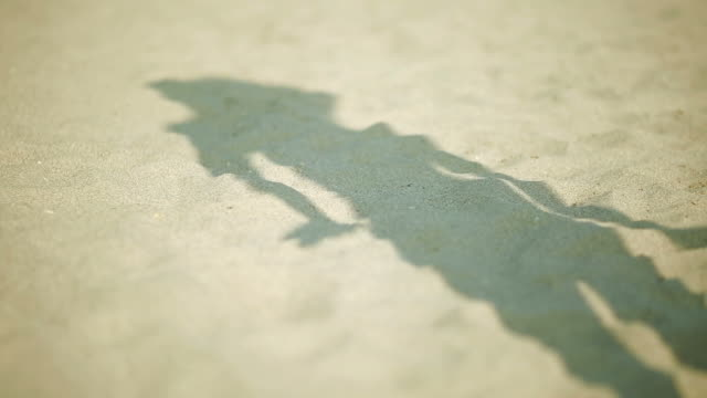 Woman's shadow on the sand at the beach as she dances video