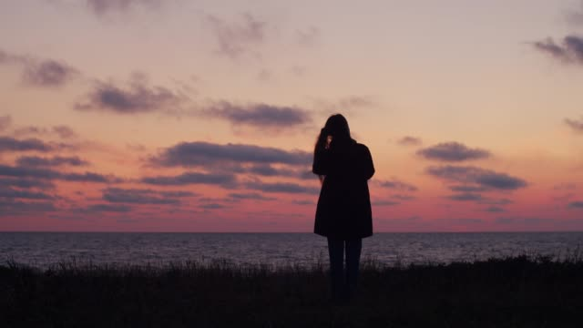 womans silhouette standing by sea at sunset alone - guardare fisso video stock e b–roll