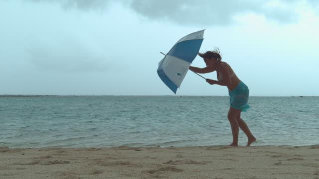 vídeos de stock e filmes b-roll de woman's umbrella gets broken while she walks down the sandy tropical beach. - guarda chuva