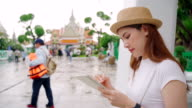 istock Women aged 20-30 years old Asian descent or save something to the notebook as she travels at the Temple of Dawn in Thailand. 1199586242