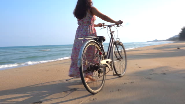 women and bicycles on the beach