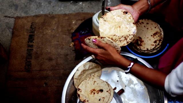 Mujeres aplicar mantequilla en chapati - vídeo