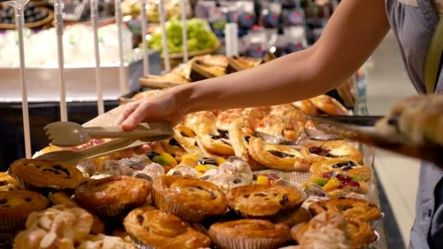 女性は、スーパーでパンを選んでいます。 ビデオ