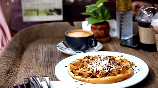 Women are eating waffle in coffee shop.