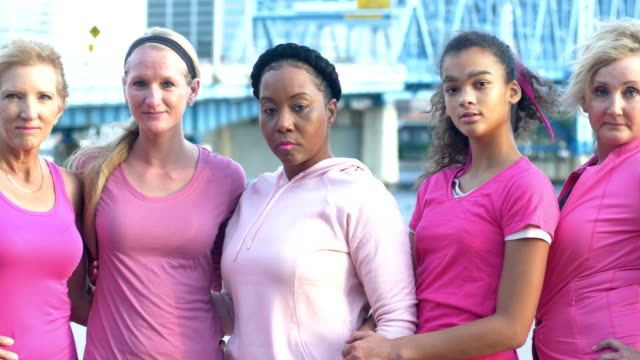 women at breast cancer awareness event, in a row - fianco a fianco video stock e b–roll