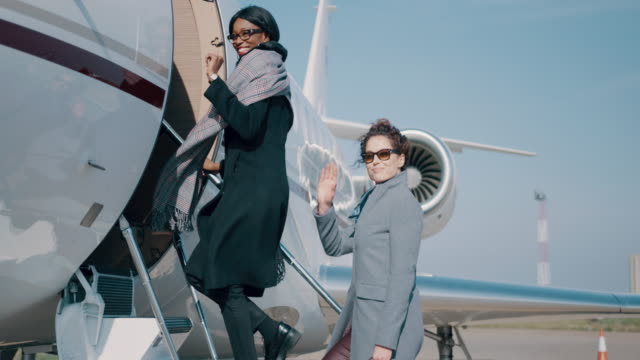 women at the airport - wchodzić na pokład filmów i materiałów b-roll