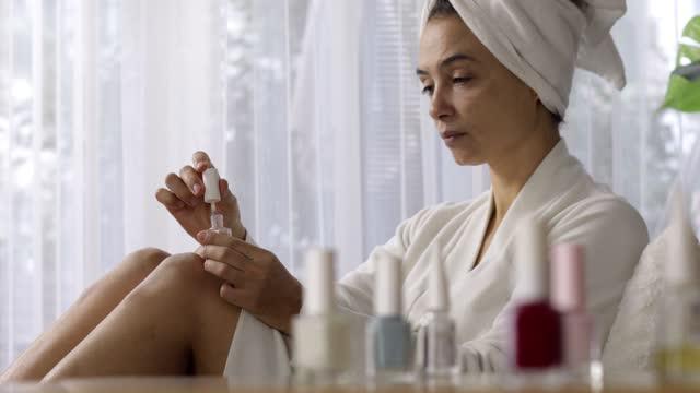 Women beauty treating herself by polish fingernails after bath