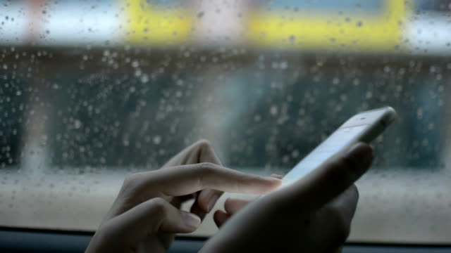 Women behind car window using smartphone in a rainy day. video