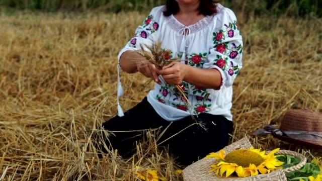 women braiding wreath from sunflowers and wheat on the meadow. - молдавия стоковые видео и кадры b-roll