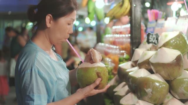 women buying coconut on street food ,thailand - video di bancarella video stock e b–roll