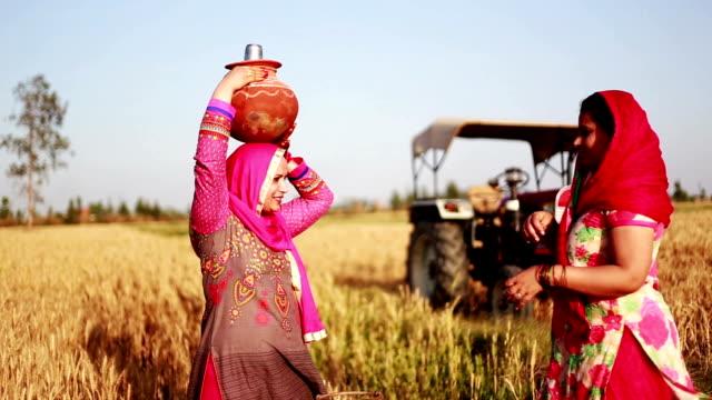 Women carrying water pot on head - video