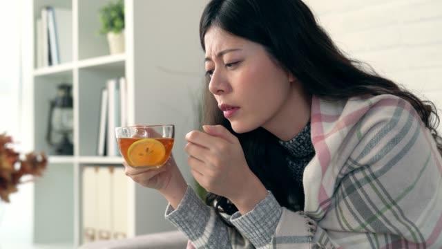 women catch cold and drinking hot lemon tea - flu shot стоковые видео и кадры b-roll