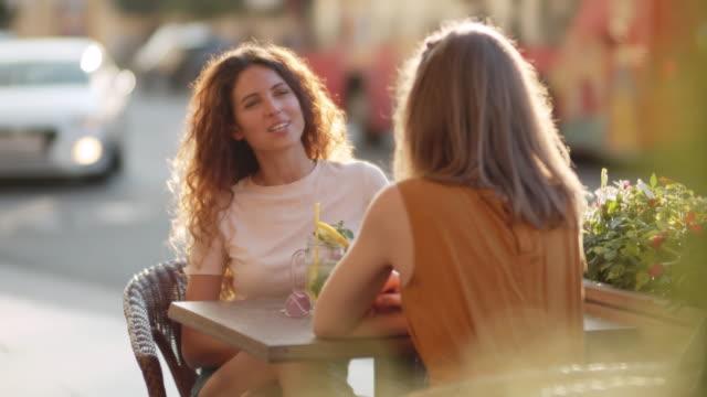 夏の日に屋外カフェでおしゃべりする女性たち - パティオ点の映像素材/bロール