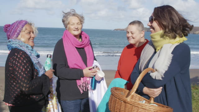 4 women chatting together on a coastal path as they get ready to head down to the beach.