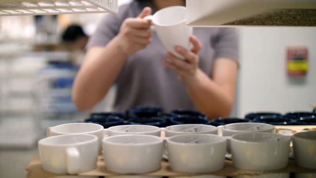 women choose a cup in the store , slow motion - porcellana video stock e b–roll