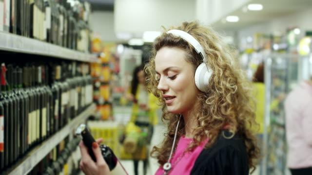 Women choosing bottle of wine and listening music on headphones in supermarket