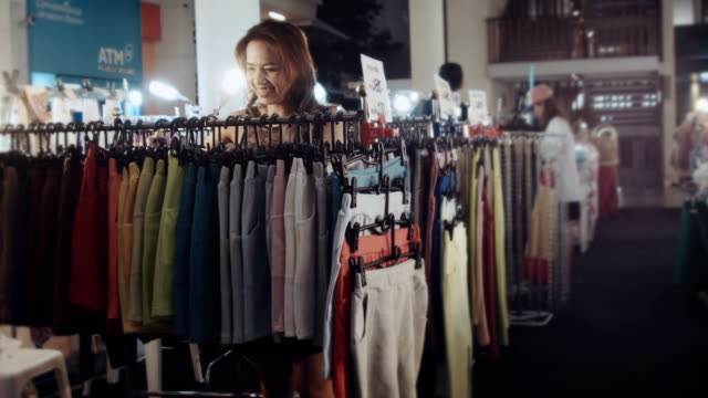 women choosing clothes in fashion store video