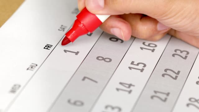 Women circles first day of the month and year on calendar