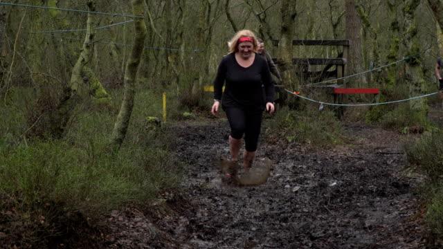 women competing in mud run through woodland - slow motion - 40 49 lat filmów i materiałów b-roll