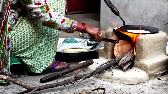 Mujeres cocinar alimentos en Mud estufa en su casa - vídeo