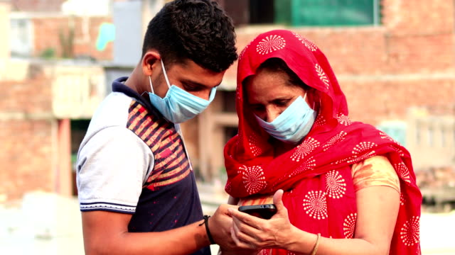 Women covering her face with pollution mask for protection from viruses and using smartphone with her son video