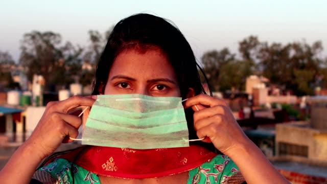 stockvideo's en b-roll-footage met vrouwen die haar gezicht met verontreinigingsmasker voor bescherming tegen virussen behandelen - india