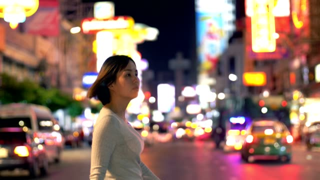 women crossing the road in bangkok chinatown at night - città diffusa video stock e b–roll