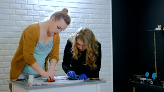 Women decorators, designers painting wooden circle decoration video