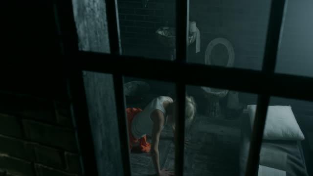 Women doing push-ups on floor in prison cell video