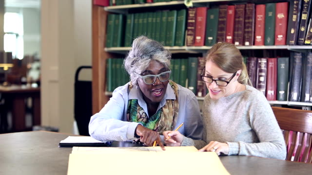 Women doing research together in library, with big book