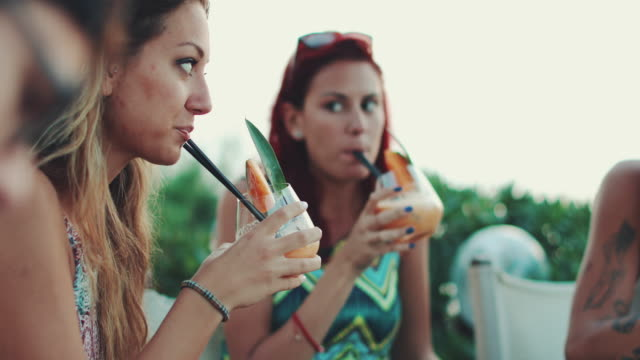 Women drinking fruit cocktail during aperitif by the sea Women drinking fruit cocktail during aperitif by the sea beach party stock videos & royalty-free footage