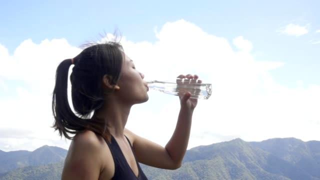 women drinking water after run, slow motion - acqua potabile video stock e b–roll