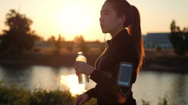 Women drinking water after running in sunset time