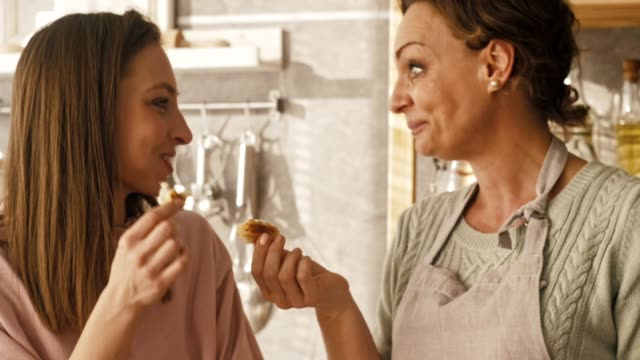 Women eating fresh homemade pastry Mature woman and her daughter are enjoying taste and scent of freshly baked pastry at the kitchen counter. tasting stock videos & royalty-free footage