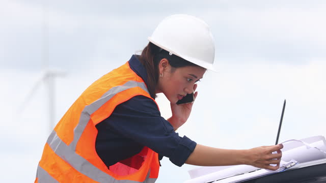 Women engineer using mobile phone and laptop for working on-site at wind turbine farm