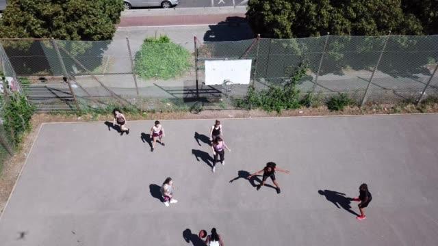 Women enjoying basketball match during summer